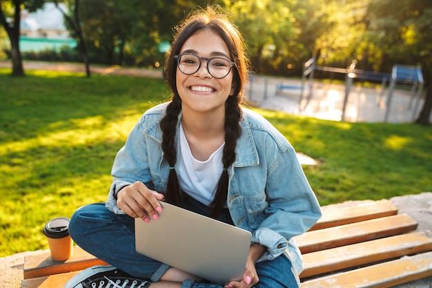 Vrolijk studentenmeisje zittend op een bankje in het park, studerend op laptopcomputer