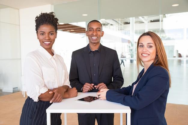 Vrolijk succesvol team van drie die in bureauggang stellen