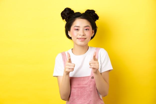 Vrolijk tiener aziatisch meisje wijzende vingers op camera en glimlachen, aanmoedigen of uitnodigen, compliment maken, mooi werk prijzen, staande op geel.