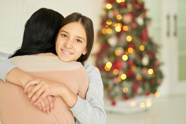 Vrolijk tienermeisje knuffelt haar moeder, glimlacht naar de camera terwijl ze thuis poseert, versierd voor kerstmis. familie, jeugd, nieuwjaar kerstviering concept