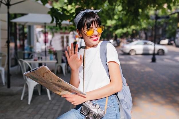 Vrolijk trendy meisje met zwaaiende hand in zilveren ring en glimlachen, wegkijken