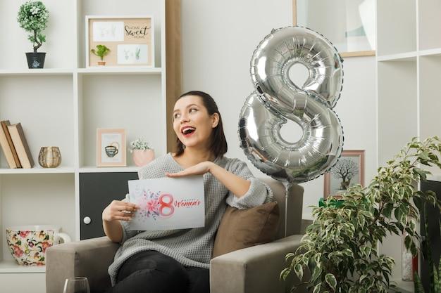 Vrolijk uitziend mooi meisje op een gelukkige vrouwendag met een wenskaart zittend op een fauteuil in de woonkamer