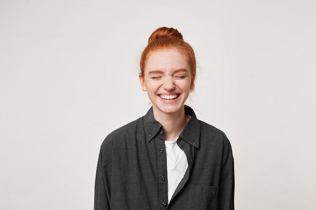Vrolijk veerkrachtig roodharig meisje met een knot op haar hoofd lacht oprecht