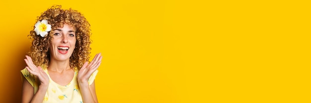 Vrolijk verrast krullend meisje met een tropische bloem in haar haar op een gele achtergrond.