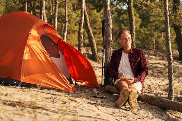 Vrolijk volwassen sportief mannetje ontspant in het bos met tent en gebruikt een tablet in de buitenlucht