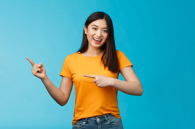 Vrolijk vriendelijk aziatisch schattig meisje met donker kapsel levendig wijzend naar links introduceert geweldige nieuwe kopieerruimte, breed glimlachend brede, vrolijke grijns, blije blauwe achtergrond, aanbevelen link.