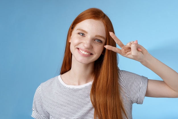 Vrolijk vriendelijk prachtig roodharig meisje dat vrolijk kijkt toont vredesoverwinningsteken kantelend hoofd schattig glimlachend breed witte tanden plezier uitdrukken positiviteit optimisme, staande blauwe achtergrond.