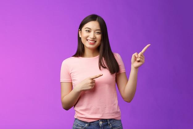 Vrolijk vriendelijk teder aziatisch glimlachend meisje dat naar rechts wijst en promo laat zien, introduceert nieuw product grijns...
