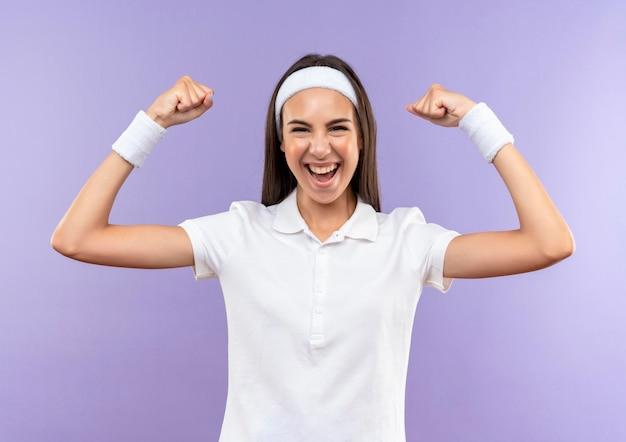 Vrolijk vrij sportief meisje met hoofdband en polsbandje gebaren sterk geïsoleerd op paarse muur purple