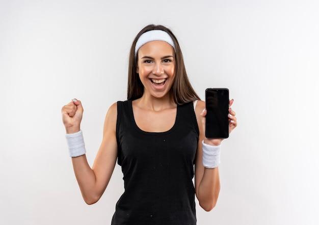 Vrolijk vrij sportief meisje met hoofdband en polsbandje met mobiele telefoon en vuist geïsoleerd op een witte muur