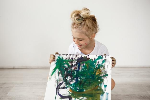 Vrolijk, vrolijk, glimlachend met haar tanden en neerkijkend op haar foto kleine blonde. europees vrouwelijk kind dat witte t-shirtzitting op de vloer draagt en beeld houdt.