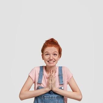 Vrolijk vrouwelijk gebed met sproeten houdt de handpalm tegen elkaar gedrukt