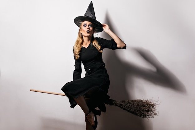 Vrolijk vrouwelijk model in lange zwarte jurk en magische hoed carnaval voorbereiden. binnen schot van blonde heks met oude bezem.