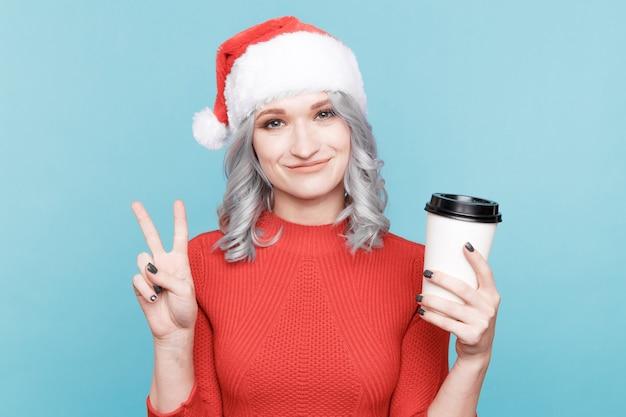 Vrolijk vrouwelijk model in rode kerstman hoed met een kopje koffie en glimlachen.