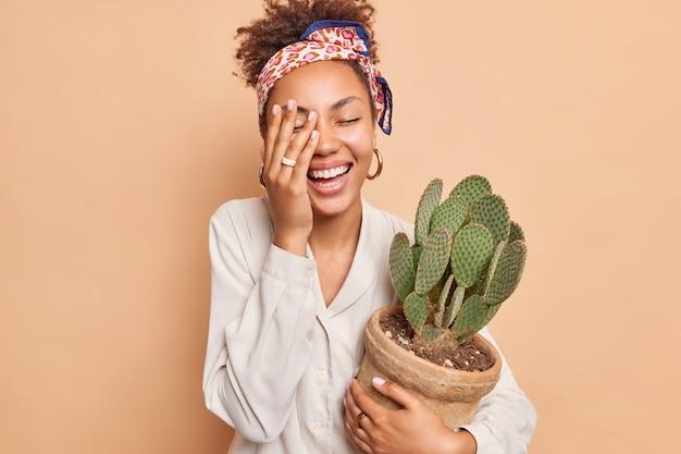 Vrolijk vrouwelijk model maakt gezicht palm glimlacht breed heeft een gelukkige stemming omarmt pot met cactus draagt wit overhemd en hoofddoek geïsoleerd over beige muur zorgt voor kamerplanten