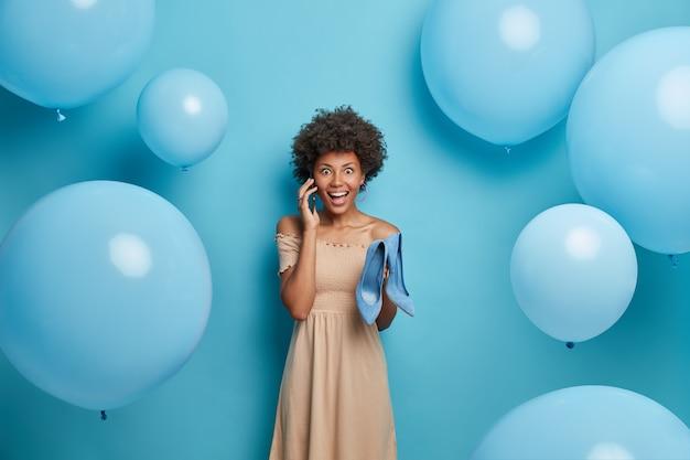 Vrolijk vrouwelijk model met donkere huid houdt modieuze schoenen op hoge hakken, heeft telefoongesprek, draagt beige jurk, modellen in blauwe muur, luchtballonnen rond. stijl en kledingconcept