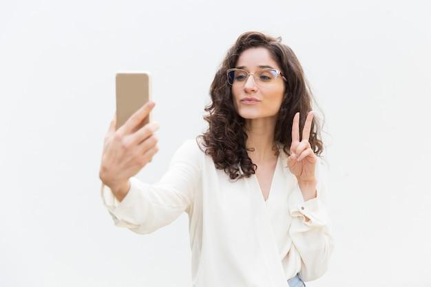 Vrolijk vrouwenmeisje die selfie op smartphone nemen