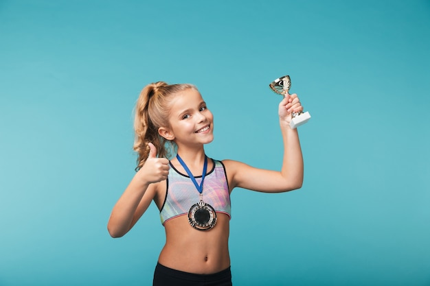 Vrolijk weinig sportenmeisje die de overwinning vieren die over blauwe muur wordt geïsoleerd, die een gouden medaille draagt, een trofee toont