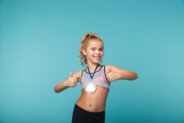 Vrolijk weinig sportenmeisje die de overwinning vieren die over blauwe muur wordt geïsoleerd, die een gouden medaille draagt