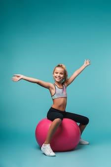 Vrolijk weinig sportenmeisje, zittend op een geschiktheidsbal die over blauwe muur wordt geïsoleerd