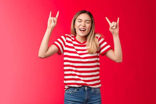 Vrolijk wild roekeloos blond aziatisch meisje dat plezier heeft en de controle verliest met rocknroll-teken geniet van geweldig...