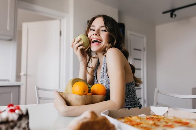 Vrolijk wit meisje dat smakelijke appel en sinaasappel eet. romantisch vrouwelijk model dat van dieet met gezond voedsel geniet.
