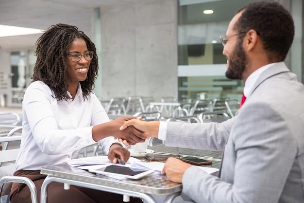 Vrolijk zakenmensen die overeenstemming bereiken