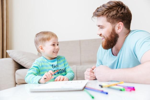 Vrolijk zoontje en vader tekenen en plezier maken thuis