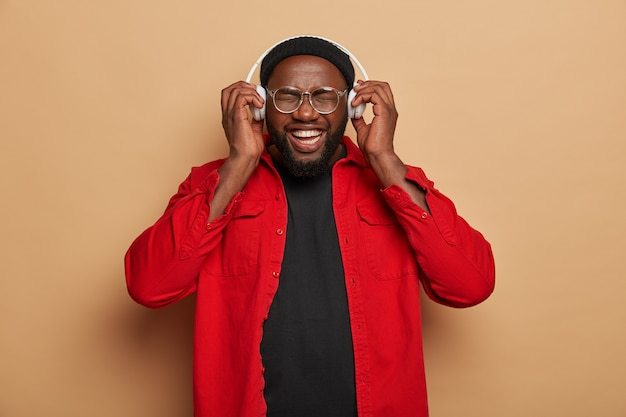 Vrolijk zwart ongeschoren mannelijk model verheugt zich op het luisteren naar favoriete muziek in de headset, loenst gezicht van gelach