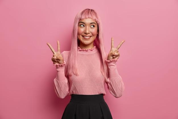 Vrolijke, aangenaam uitziende vrouw met lang roze haar, toont overwinning of vredesgebaar, lacht vreugdevol en voelt zich gelukkig, kijkt opzij, in goed humeur