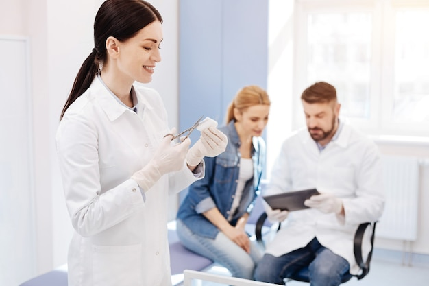 Vrolijke aangename jonge vrouw met een schaar en een stuk verband afsnijden tijdens het assisteren in het kantoor van de dokter