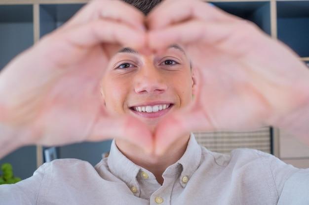 Vrolijke aanhankelijke tiener man neemt romantisch selfie portret camera kijken door hart van samengevoegde vingers. verliefd jongedame schiet liefdesbekentenis aan geliefde man op video op valentijnsdag