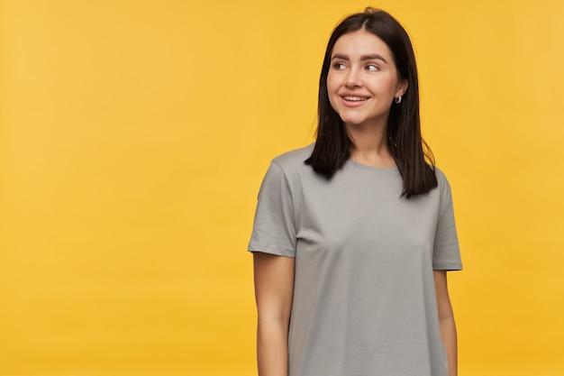 Vrolijke aantrekkelijke, aantrekkelijke brunette jonge vrouw in een grijze t-shirt staande advertentie die wegkijkt naar de zijkant op copyspace over gele muur