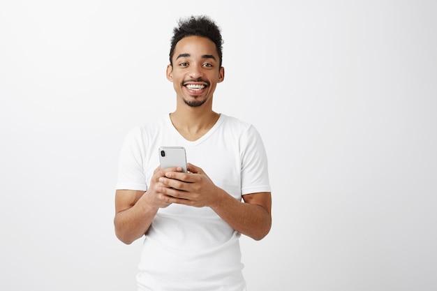 Vrolijke aantrekkelijke afro-amerikaanse man in wit t-shirt met mobiele telefoon, glimlachend