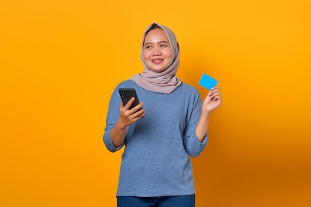 Vrolijke aantrekkelijke aziatische vrouw die mobiele telefoon vasthoudt en creditcard toont over gele achtergrond