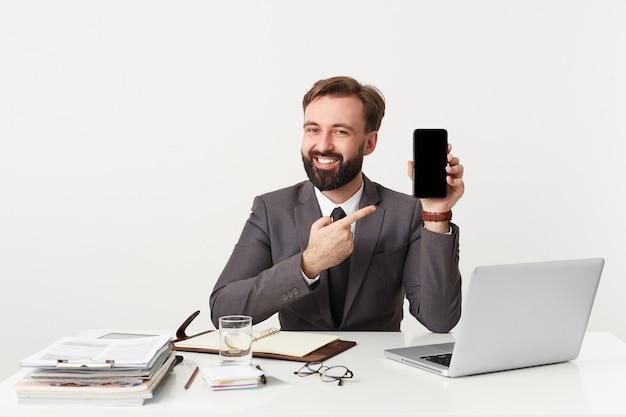 Vrolijke aantrekkelijke bebaarde zakenman, topmanager zittend op het bureaublad op kantoor, camera kijken en glimlachend, gekleed in een duur pak met stropdas, wil uw aandacht vestigen op zijn smartphone.