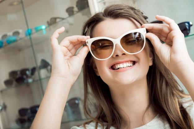 Vrolijke aantrekkelijke brunette die nieuwe zonnebril plukt met behulp van winkelmedewerker