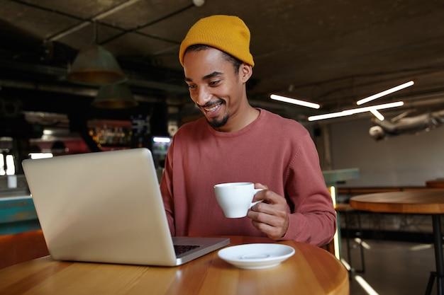 Vrolijke aantrekkelijke donkere jonge zakenman zittend op koffiehuis interieur, op afstand werken met moderne laptop en koffie drinken, positief op het scherm kijken
