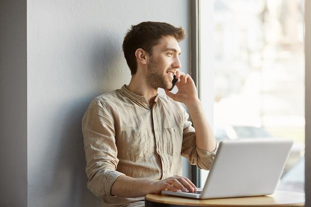 Vrolijke aantrekkelijke geschoren man zittend in coworking ruimte, werken op laptopcomputer en praten over de telefoon met vriendin over datum in de avond.