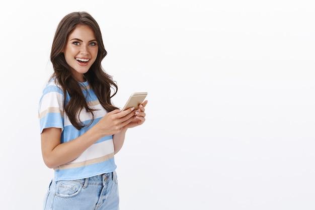 Vrolijke aantrekkelijke glamourvrouw met lang krullend kapsel staat half gedraaid, houdt smartphone camera vast met brede blije glimlach die opwindend nieuws vertelt, bericht navertelt, mobiele game of app speelt