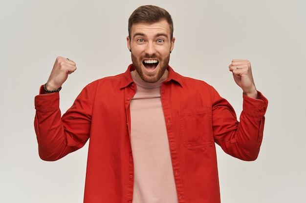 Vrolijke aantrekkelijke jonge bebaarde man in rood shirt ziet er opgewonden uit en viert de overwinning op de witte muur