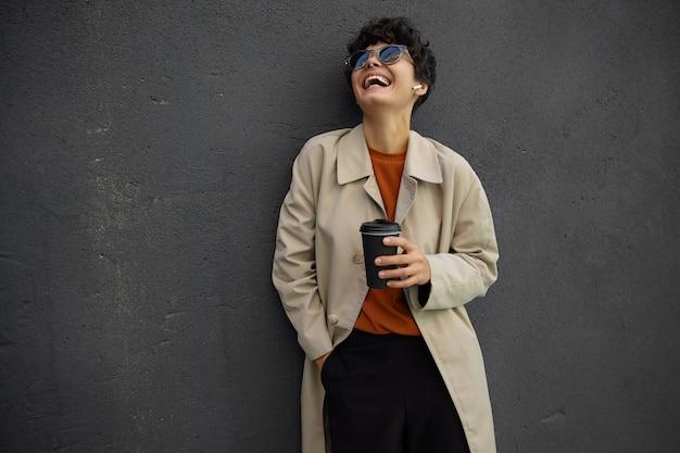 Vrolijke aantrekkelijke jonge krullende vrouw met donker kort haar gelukkig lachen en haar hoofd achterover gooien, staande boven de stedelijke omgeving terwijl ze koffie drinkt voor de werkdag