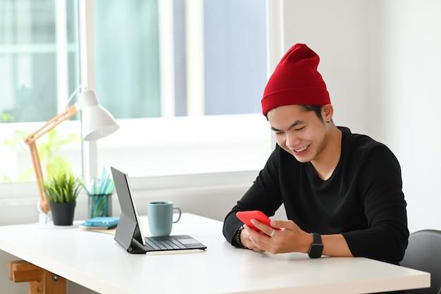 Vrolijke aantrekkelijke jonge man grafisch ontwerper glimlachend en met behulp van slimme telefoon aan zijn bureau in moderne kantoren.