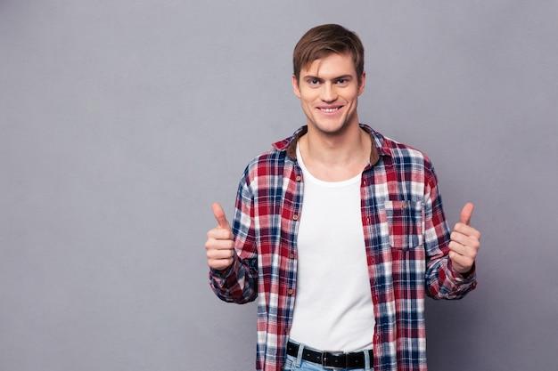 Vrolijke aantrekkelijke jonge man in geruit hemd duimen opdagen over grijze muur