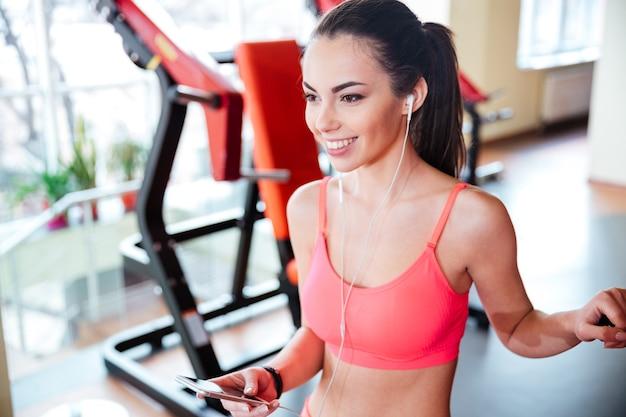 Vrolijke aantrekkelijke jonge vrouw atleet luisteren naar muziek en het gebruik van mobiele telefoon in de sportschool