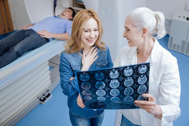 Vrolijke aantrekkelijke jonge vrouw die glimlacht en opgelucht wordt terwijl ze met de dokter praat over de diagnose van haar man