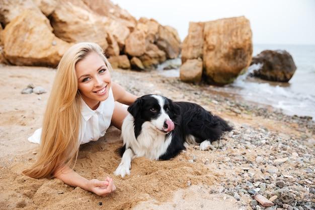 Vrolijke aantrekkelijke jonge vrouw die met hond op het strand rust