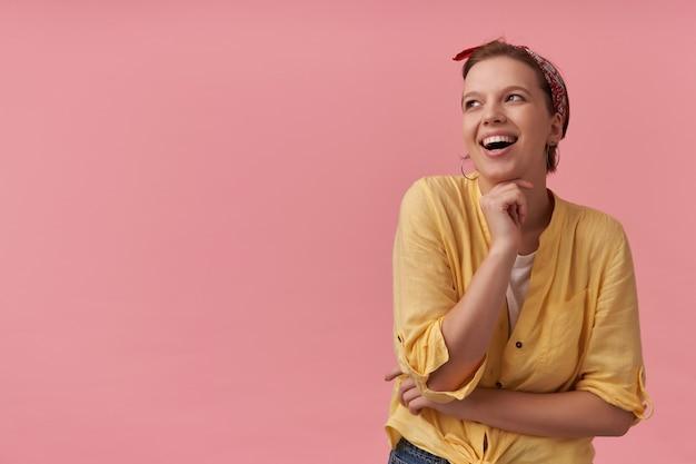 Vrolijke aantrekkelijke jonge vrouw in geel overhemd met rode hoofdband op het hoofd houdt de handen gevouwen en kijkt weg naar de zijkant over de roze muur