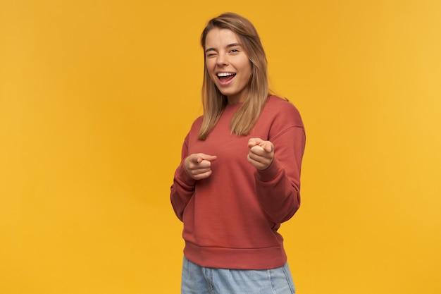 Vrolijke aantrekkelijke jonge vrouw in terracotasweatshirt knipoogt en wijst op u met beide handen over gele muur