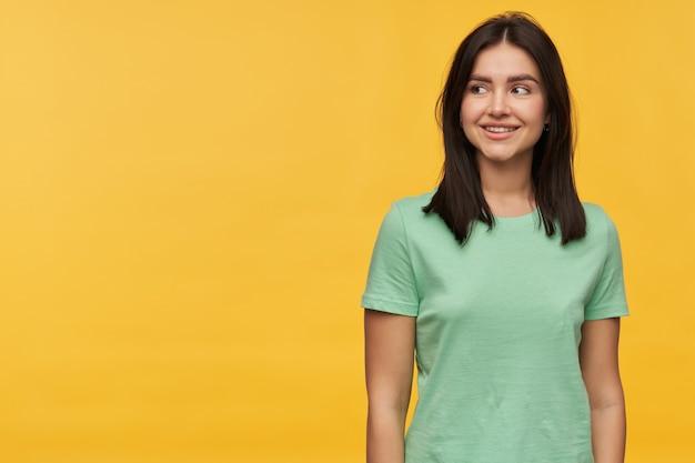 Vrolijke aantrekkelijke jonge vrouw met donker haar in mint tshirt staande en wegkijkend naar de zijkant op copyspace geïsoleerd over gele muur